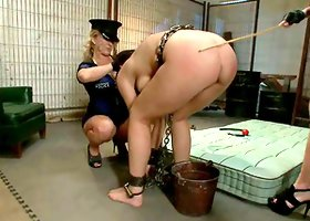 Chained brunette gets whipped and toyed by a policewoman